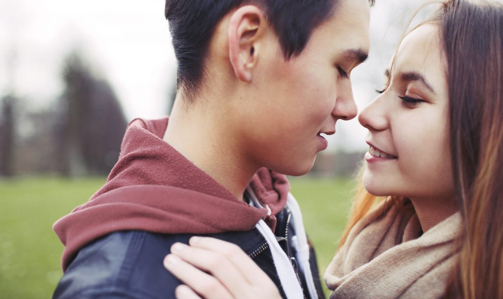 close-up-image-of-romantic-young-couple-in-park-asian