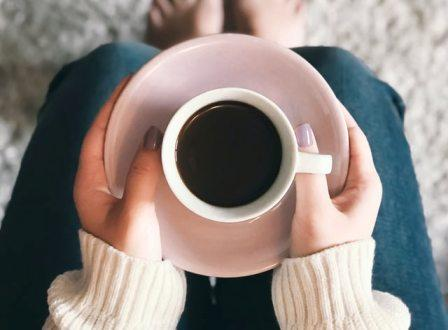 Someone holds a saucer and mug filled with black coffee that will help her take a coffee nap to make her feel more energized.